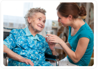 caretaker giving a glass of water to an elderly woman