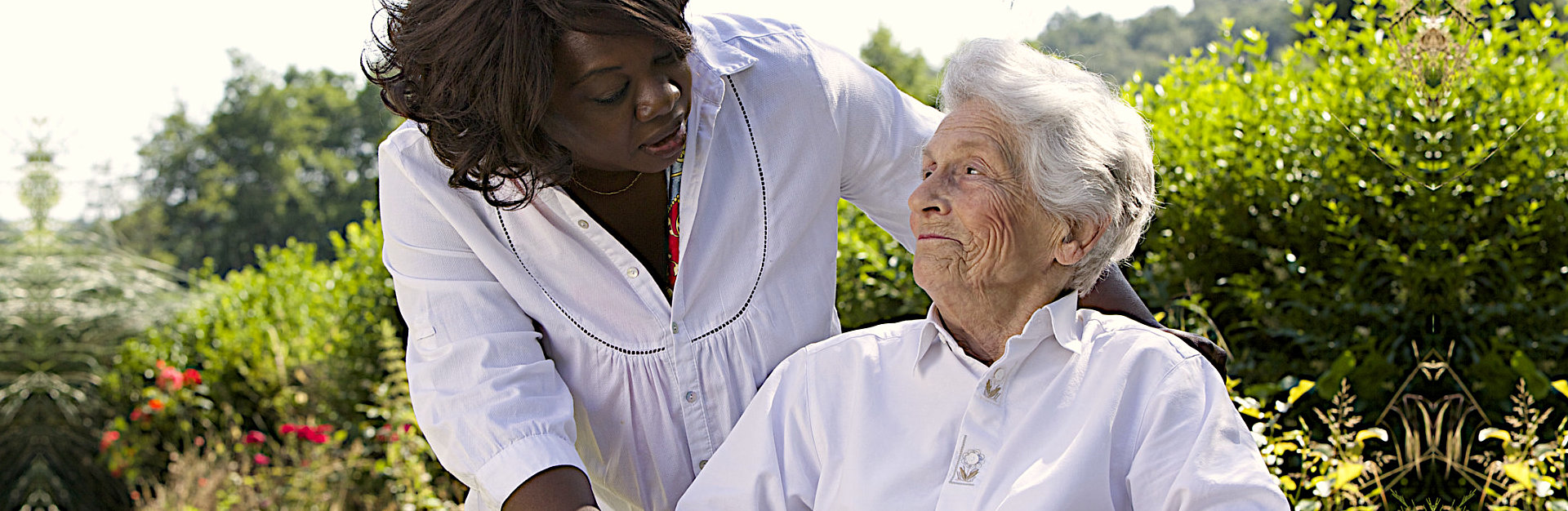 helpful african american caregiver talking to a disabled senior woman